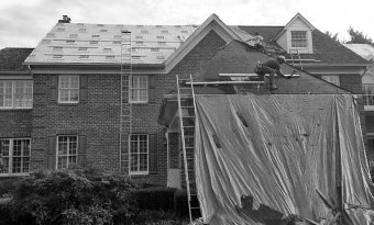 workers repairing the front side of the roof